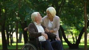 Interessierende Frau, die ihren Ehemann im Rollstuhl, küssend, Familie stützt stock video