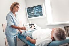 Interessierende junge Krankenschwester, die ob geduldiges Gefühls-O.K. fragt stockbild