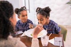 Interessierende liebende Mutter, die ihrer Tochter isst Teigwaren in der Cafeteria hilft lizenzfreies stockfoto