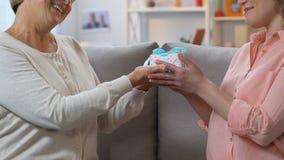 Interessierende Mutter, die der erwachsenen Tochter Geschenk, angenehme Überraschung für Geburtstag gibt stock footage