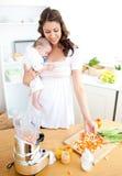 Interessierende Mutter, die Gemüse für ihr Schätzchen vorbereitet Lizenzfreie Stockbilder