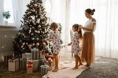 Interessierende Mutter flicht die Borte ihrer kleinen Tochter, während Sekundentochter einen Baum des neuen Jahres im gemütlich stockbild
