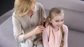 Interessierende reife Mutter, die Töchter blondes Haar, Schönheitszeit, Verhältnis kämmt lizenzfreie stockfotos