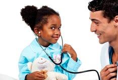 Interessierender Doktor, der mit seinem jungen Patienten spielt Stockbild