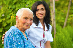 Interessierender Doktor mit kranker älterer Frau draußen Stockfotos