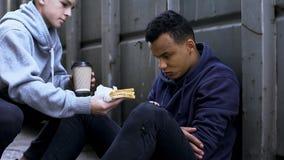 Interessierender freiwilliger Junge holt dem obdachlosen Jugendlichen, nettes Herz, Nächstenliebe Abendessen stockfotos