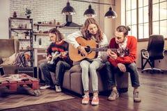 Interessierender Freund, der seinem schönen Mädchen spielt die Gitarre hilft stockfoto