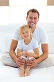 Interessierender Vater mit seinem kleinen Mädchen, das auf Bett sitzt Lizenzfreies Stockfoto