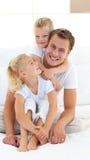 Interessierender Vater mit seinen Kindern, die auf Bett sitzen Lizenzfreie Stockfotografie