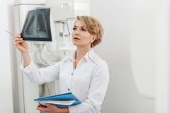 Interessierte Ärztin, die Röntgenbild hält Stockfotos