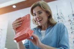 Interessierte Frau, die Schauspielkasten betrachtet stockfoto