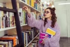 Interessierter ansprechender Leser, der aktiv neue Bücher sammelt lizenzfreies stockfoto