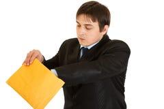 Interessierter junger Geschäftsmann, der Paket überprüft Lizenzfreie Stockfotos