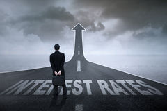 Interest rate and businessman on the road. Concept of growing interest rates. Entrepreneur standing on the highway with Interest Rates text on it Stock Photography