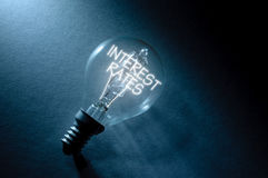 Interest rates. Bulb with interest rates lit up inside Royalty Free Stock Images