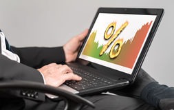 Interest rates concept on a laptop. Businessman watching interest rates concept on a laptop Royalty Free Stock Images