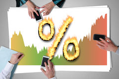 Interest rates concept placed on a desk. With hands using smartphones Royalty Free Stock Photos