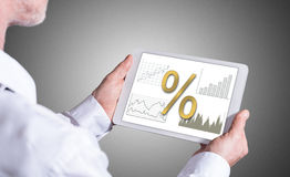 Interest rates concept on a tablet. Man holding a tablet showing interest rates concept Stock Photography