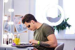 Interested accurate man with tattooed hand observing new makeup. Skincare products. Interested accurate man with tattooed hand observing new makeup while stock photography