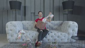 Joyful female unwrapping birthday gift box at home. Interested adult birthday girl in anticipation tearing wrapping paper on gift box while sitting on sofa after stock footage