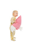 Interested baby standing with heart shaped pillow Royalty Free Stock Images