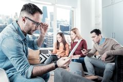 Interested bespectacled man sitting and overlooking the document. What is this. Interested handsome bespectacled men sitting in the room near his friends Stock Photos