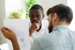 Interested black client listening to financial advisor explainin. Interested black client listens to financial advisor explaining new project investment, african Royalty Free Stock Images