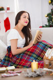 Interested brunette reading on the couch  with cover Stock Photo