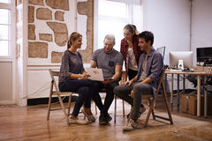 Interested business team looking at chart. Interested young business team looking at a chart one of them is holding up while gathered in a semi circle in an open Royalty Free Stock Photography