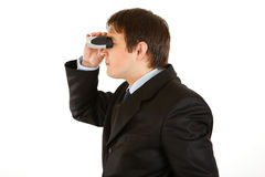 Interested businessman looking through binoculars. Interested young businessman looking through binoculars isolated on white Royalty Free Stock Photo