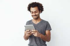 Interested and concentrated young african man looking at tablet playing a platformer game and enjoying new levels over Stock Photos