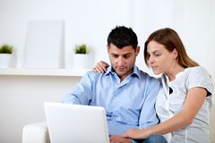 Interested couple browsing on laptop Royalty Free Stock Image