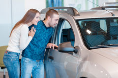 Interested couple examines a new car in showroom Stock Image