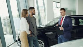 Interested couple man and woman are talking to manager in car dealership while he is telling them about luxury auto