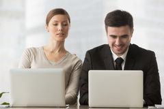 Interested curious businesswoman looking at businessman laptop s. Interested curious corporate spy looking at colleagues laptop, spying on rival, cheating on stock photos