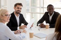 Interested diverse employees listen to colleague talking. Interested diverse workers sit at table listen to female colleague talking, multiethnic business people stock photos