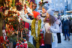 Interested family couple with teen girl choosing Christmas decor. Ation at fair Royalty Free Stock Photos