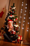 Interested girl near Christmas tree with present Royalty Free Stock Images