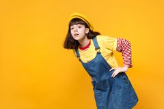 Interested girl teenager in french beret, denim sundress looking attentively, standing with arms akimbo isolated on royalty free stock images