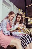Interested girls studying together in cafe using manuals. Discussing information. Interested girls studying together in cafe using manuals and educational books royalty free stock images