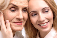 Interested glances of smiling women. Joyful mother and daughter are looking aside with bright smile. Portrait Stock Photos