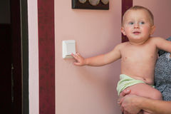 Interested little boy turning off the light-switch Royalty Free Stock Photo