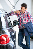 Interested man  examines a new car in showroom Royalty Free Stock Photo