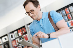 Interested man testing technological capabilities of gadget at store. I really like this gadget. Concerned man wearing glasses standing at a display of a store royalty free stock photography