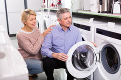 Interested mature couple chooses washing machine for their house. In shop of household appliances refrigerator for your house Royalty Free Stock Photo