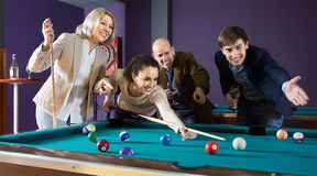 Interested middle class people playing pool game in billiard clu Stock Photo