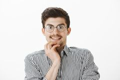Interested nerdy office manager looking with temptation through glasses at new computer in store, smiling nervously. Wanting to buy new gadget, standing Royalty Free Stock Photography