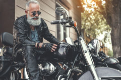 Interested old man checking motorbike Stock Photo