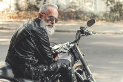 Interested old man ready for riding motorcycle Stock Image