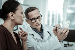 Interested patient attentively looking on the white heart. Doctor having appointment. Interested patient attentively looking on the white heart and listening to royalty free stock photos